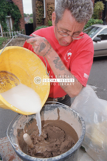 Builder mixing mortar in preparation for repointing ridge tiles,