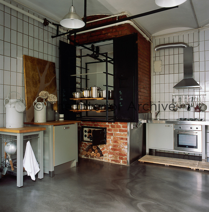 The kitchen area was converted from a butcher's shop and still has the original wall tiles. An existing oven is utilised as a wine rack and log store with shelving above. The use of various shades of grey and blue soften the industrial feel of the room
