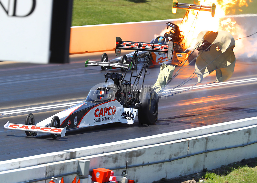 May 21, 2017; Topeka, KS, USA; NHRA top fuel driver Steve Torrence (near) alongside Clay Millican who explodes an engine on fire during the Heartland Nationals at Heartland Park Topeka. Mandatory Credit: Mark J. Rebilas-USA TODAY Sports