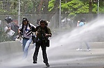 photojournalist and Students of the Antioquia University are sprayed with water while they a hold protest against US goverment in Medellin for the arrival of US. President Barack Obama to the Sixth Summit of the Americas in Cartagena, Colombia, 13/04/2012. Photo by Fredy Amariles / viewpress.