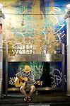 Musician You Waki busks under the railway tracks at  Shimokitazawa, Setagaya Ward, Tokyo, Japan..Photographer: Robert Gilhooly