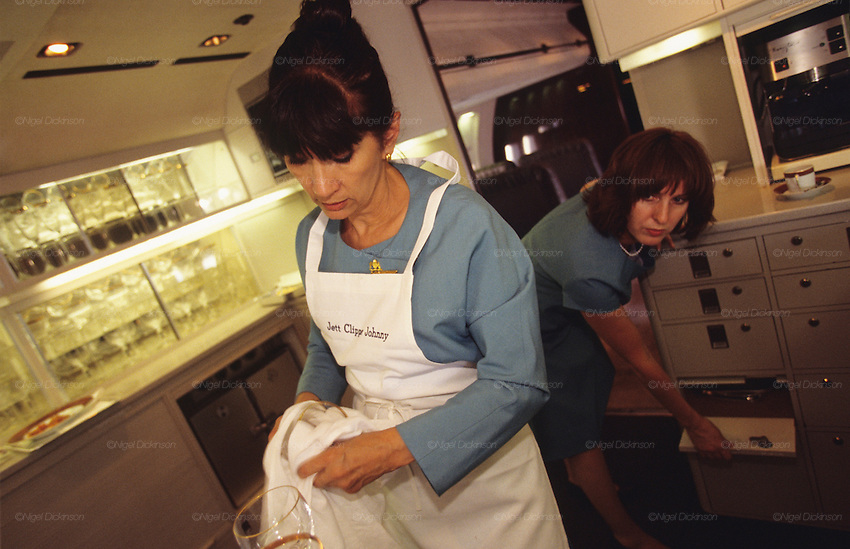 "Crew of John Travolta's jumbo jet. Stewards and stewardesses preparing food for guests..John Travolta is pilot of his very own jumbo jet, a 1964 Boeing 707-100 series. In 2003, John Travolta flew his jumbo jet around the world, in partnership with Quantas, to rekindle confidence in commercial aviation, and to remind us that elegance and style are a part of flying. The crew are dressed in tailor made authentic uniforms from the Quantas museum. The men's uniforms are styled on British Naval uniforms and the ladies' designed by Chanel. His jumbo jet sports a personalised number plate N707JT which speaks for itself. The aircraft is named ""Jett Clipper Ella"" dedicated to his son and daughter. This jumbo together with his other aircraft are housed in purpose built hangars at his home in Florida, USA."