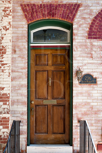 Old brick row house doors in the better sections of older eastern American towns can be quite beautiful when decorated to welcome from street view. The residents take good care of them, make a display, and value their charm. The doors themselves are often original to the buildings. They make a very interesting art gallery of their own while casually walking the old streets on a little door tour, and there is a lot of variety according to an owner&rsquo;s taste. The doors exist in a modern day while being a direct line through history to now, and are still in use most every day.<br /> <br /> None of the two story row homes are wider than about fifteen feet, if that. The properties continue to the alley through equally narrow back yards leading away from a small roofed porch, the yards usually crammed with greenery and flowers in the summers and set off by delineating fences. It&rsquo;s a close elbow-to-elbow way of living that also has shared walls. <br /> <br /> This particular home is older than the Civil War. Made of hand thrown local brick, it is part of a well-kept three block group of them down one street in an old town center that is today ringed by a series of much larger modern expansions. This elegant door is nearly a work of art with the dusty rose brick and the fanned brickwork keystoning in a complimentary red above. A warm brown wooden door trimmed in hunter green finishes it off nicely.<br /> <br /> Monthly Newsletter sign up at Dierks Photo on Facebook...