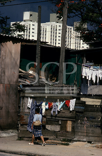 Sao Paulo, Brazil. Shanty town (favela) houses made from re-used wood etc. with high-rise apartment buildings behind.