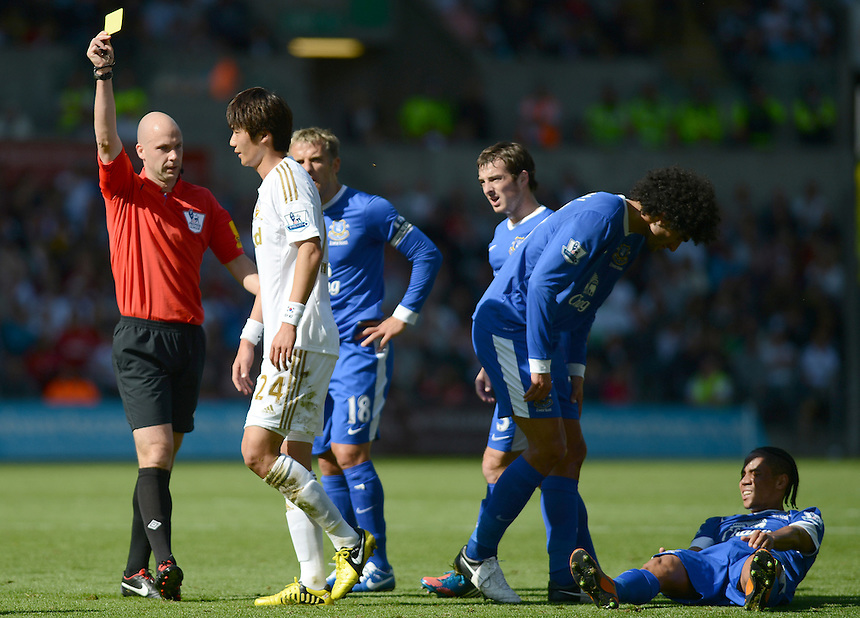 Referee Anthony Taylor shows Swansea City's Ki Sung-Yong the Yellow Card after his tackle on Everton's Steven Pienaar ..Football - Barclays Premiership - Swansea City v Everton - Saturday 22nd September 2012 - Liberty Stadium - Swansea..