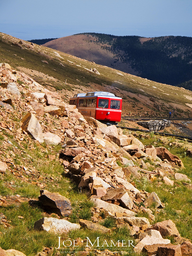 Pikes Peak cog rail train climbs to the summit of Pikes Peak. The Manitou and Pike's Peak Railway (also known as the Pikes Peak Cog Railway) is an Abt rack system cog railway in Colorado, USA, climbing the well-known mountain Pikes Peak. The base station is in Manitou Springs, Colorado near Colorado Springs..The railway is the highest in North America by a considerable margin. It was built and is operated solely for the tourist trade..