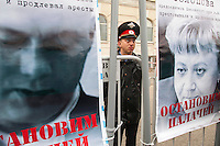 Moscow, Russia, 06/05/2013..A young policeman in Bolotnaya Square watches protesters through a gap in banners with images of imprisoned Russian opposition leaders as some 20,000 demonstrators protested against Russian President Vladimir Putin and demanded the release of political prisoners. The demonstration marked the first anniversary of a protest that descended into violence between protesters and police and resulted in over 600 arrests.
