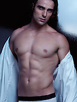 Expressive portrait of a sexy young handsome man with long hair and muscular bare torso taking off his shirt