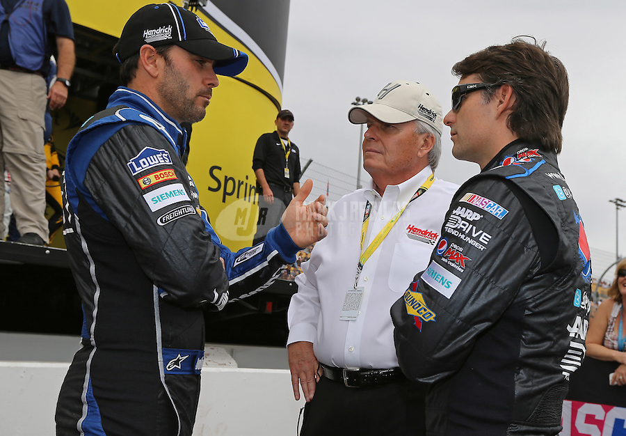 Mar. 3, 2013; Avondale, AZ, USA; NASCAR Sprint Cup Series driver Jimmie Johnson (left) and Jeff Gordon (right) talk to team owner Rick Hendrick prior to the Subway Fresh Fit 500 at Phoenix International Raceway. Mandatory Credit: Mark J. Rebilas-