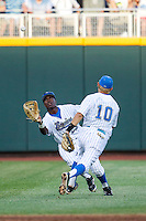 UCLA outfielder Brenton Allen (23) makes a running catch avoiding shortstop Pat Valaika (10) during Game 12 of the 2013 Men's College World Series against the North Carolina Tar Heels on June 21, 2013 at TD Ameritrade Park in Omaha, Nebraska. The Bruins defeated the Tar Heels 4-1, to reach the CWS Final and eliminate North Carolina from the tournament. (Andrew Woolley/Four Seam Images)