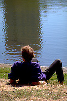 Man age 25 relaxing in sun on waterfront at Loring Park.  Minneapolis  Minnesota USA