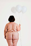 Overweight nude woman holding up white balloons