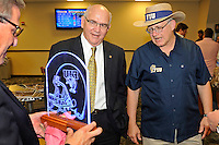 12 August 2011:  FIU Alumni Association Director Bill Draughon (center) and FIU President Mark Rosenberg (right) view an illuminated etching of an FIU football helmet being held by FIU Biscayne Bay Campus Vice Provost Steve Moll (left) during the FIU 2011 Panther Preview at University Park Stadium in Miami, Florida.