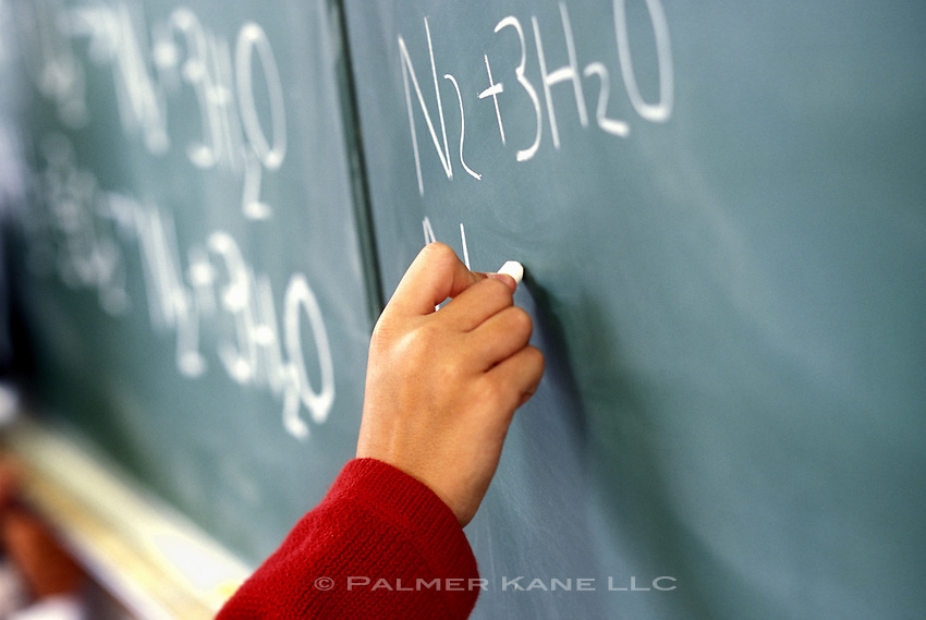 CU student writing on chalkboard in chemistry class