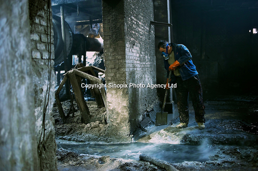 "A worker stands in acid, his trousers already burnt and full of holes, at  ""rare-earth"" processing plant near Bayon Obo, Inner Mongolia.  The plant conducts first stage processing in extremely toxic conditions where workers complain of acid burns and sores as well as head-aches. The production of ""rare-earths"" is an extremely poisenous process with plants in the U.S. being closed due to environmental concerns. China accounts for some 97% of rare earth consumed world-wide. The ""rare earth elements"" are a group of 17 elements that are essential in 25% of modern technology including cell phones, computer hard discs, and electric motors and inparticular green technology such as electric batteries and wind turbines."