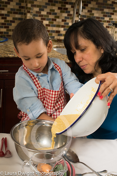 3 year old boy in kitchen at home learning to cook with mother, baking, pouring batter into bowl