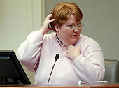 Alabama sniper victim Kellie Adams demonstrates how a bullet entered the back of her head and exited her chin during her testimony in the trial of sniper suspect John Allen Muhammad at the Virginia Beach Circuit Court in Virginia Beach, Virginia on October 22, 2003. <br /> Credit: Davis Turner - Pool via CNP