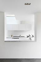 A view through an internal window to a white minimal kitchen beyond