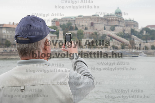 Participants takes a photo with his mobile phone at a boat ride on river Danube with the Castle of Buda in the background during the International Day for Older Persons in Budapest, Hungary on Oct. 1, 2018. ATTILA VOLGYI
