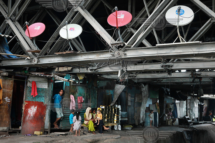 Families living under a bridge where they have fixed satellite dishes for their televisions to its structure.
