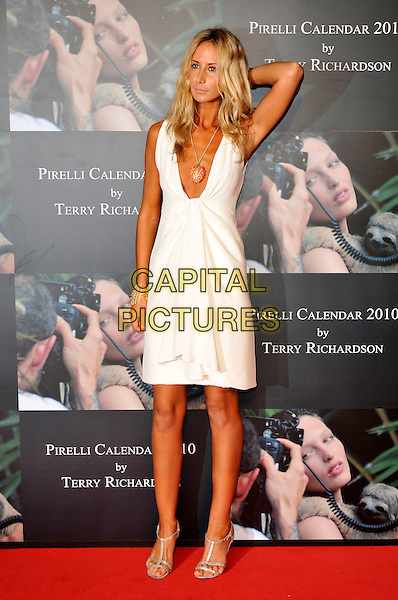 LADY VICTORIA HERVEY .Attends the Pirelli Calendar 2010 Gala Dinner, Old Billingsgate, Old Billingsgate Walk, London, England, UK,.20th November 2009..full length white dress low cut plunging neckline hand on head touching hair tanned sun tan clutch bag sandals gold cuff bracelet necklace sleeveless .CAP/PL.©Phil Loftus/Capital Pictures.