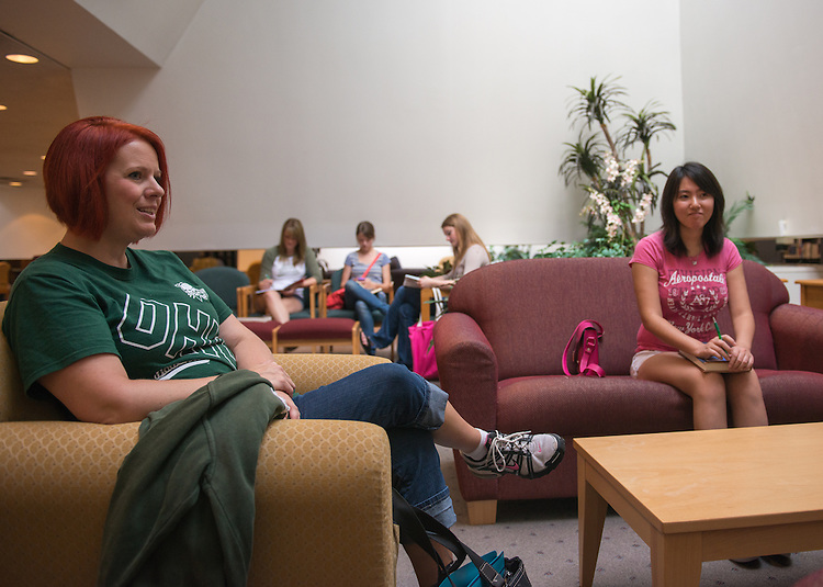Andrea Ritterbeck, left, and Xuejiao Tian, right, converse in the library at Ohio University Zanesville.