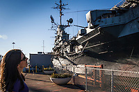 A young woman looks up at the USS Hornet Aircraft Carrier on public display at the former Naval Air Station Alameda in Alameda, California.