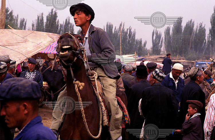 ©Chris Stowers/Panos Pictures..Ethnic Uiygur Muslim boy rides his horse through the famed Sunday Market in Kashgar, Xinjiang Province, NW China.