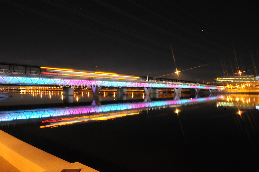 Tempe, Arizona. A colorful view of the Light Rail bridge at Tempe Town Lake. The upper yellow, white and red lights above the bridge are those of  moving light rail cars going through the bridge at night time. Photo by Eduardo Barraza © 2015
