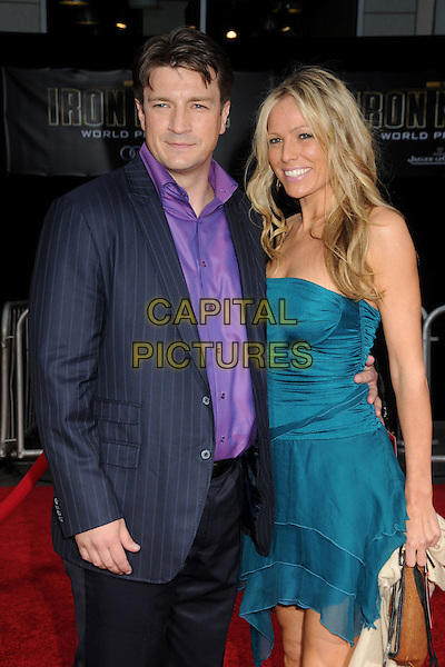 """NATHAN FILLION & GUEST .""""Iron Man 2"""" World Premiere held at the El Capitan Theatre, Hollywood, California, USA, 26th April 2010..arrivals half length navy blue pinstripe suit green strapless teal dress purple shirt .CAP/ADM/BP.©Byron Purvis/AdMedia/Capital Pictures."""