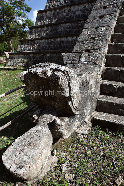 Head of serpent resting on the ground at the base of the Ossuary Pyramid, 800-900 AD, Toltec Architecture, Chichen Itza, Yucatan, Mexico. This pyramid was probably used for the cremations. Picture by Manuel Cohen