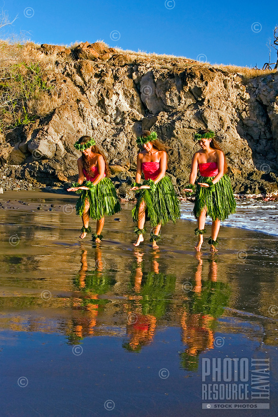 Three hula dancers in ti leaf skirts dance at the water's edge with their reflection at Olowalu, Maui.
