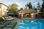 Plenty of blue sky and wispy white clouds show off this peaceful, early  evening summer view of a beautifully manicured, poolside landscape featuring geometrically patterned concrete pavers intersperced with lush green grass lawn, containers of mixed annuals, a long beautiful blue swimming pool with built in tiled spa glowing blue in the low angled sunshine, matching chaise lounge chairs and dining tables with orange red umbrellas, and a poolside cabana building with outdoor fireplace in this Northwest summer scene in a suburban community east of Seattle.