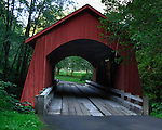 This beautiful red, wooden, covered brdge was built in 1938 for $1,500. It spans the north fork of the Yachats River in Oregon. The bridge, constructed by Otis Hamer, is a 42-foot, Queenpost truss-type bridge surrounded by landscaped woods-like environment.