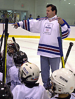 Mike Eruzione, a member of the 1980 U.S. Olympic men's hockey team, gives stick handling instructions, during a hockey clinic, sponsored by Allstate insurance, Thursday, Dec. 6, 2001, in Philadelphia. Allstate Insurance Company, the official Home and Auto Insurance sponsor of the 2002 Olympic Winter Games, launched a program that will reunite members of the 1980 Olympic Winter Games men's ice hockey team for a series of yougth clinics, and a reunion ice hockey game. (Photo by William Thomas Cain/photodx.com)