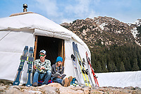 A couple relaxes at their yurt camp while on a ski trip in Kyrgyzstan.