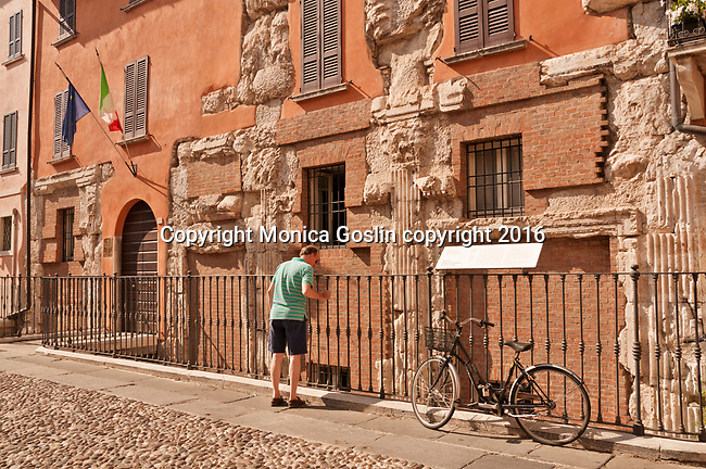 Man looking at a house made from Roman ruins, a common sight in Brescia, Italy