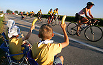Nathan Paskach, 8, of Ames, right, and his siblings, Eric, 6, and Dagney, 10, offer bananas to passing riders outside of Nevada on RAGBRAI XXXVI.