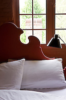 A detail of the carved headboard in the master bedroom silhouetted againt the window