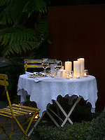 A small table draped in a lace tablecloth is set for an al fresco candlelit dinner for two