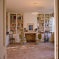 The library has low, Louis XVI chairs either side of the fireplace and the mantlepiece is decorated with a painting by Marc Chagall and a bust of the artist