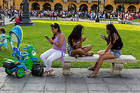 Peru, Lima.  Three Young Women Checking their Cell Phones in the Plaza de Armas, while young child walks away.