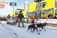 Rod Perry, one of the original dog mushers from the innaugural 1973 Iditarod Race leaves the ceremonial start of the 2011 Iditarod in Anchorage, Alaska with musher Eric Rogers riding in front on the GEE pole.