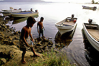 Young boys playing by water taxi boats in Truk, Micronesia.