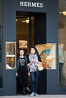 Chinese women leave Hermes clothes shop, in Nanjing Road designer shopping district, central Shanghai, China