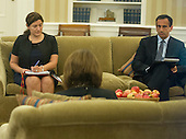 Elisa Catalano, Director for Gulf States, left, and Philip Gordon, Special Assistant to the President and White House Coordinator for the Middle East, right, are photographed through an Oval Office window as they listen in on a phone conversation between United States President Barack Obama and King Abdallah Abd al Aziz of the Kingdom of Saudi Arabia at White House in Washington, D.C. on Wednesday, September 10, 2014 as he prepares for his speech to the nation this evening. <br /> Credit: Ron Sachs / Pool via CNP