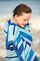 Cute young girl drying off with a beach towel, Cape Cod, MA