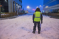 Parking volunteer Sue Mattson waits paitently in thee early morning hours on 4th avenue to guide dog mushers onto the street prior to the ceremonial start of the Iditarod sled dog race in downtown Anchorage Saturday, March 2, 2013. ..Photo (C) Jeff Schultz/IditarodPhotos.com  Do not reproduce without permission