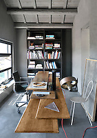 A functional, grey office space with a painted, beamed ceiling, stone walls and a concrete floor. The room is furnished with a free-standing, open bookcase, a steel office chair and a wood table with layered tops.