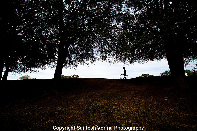 A lone child in silhouette playing with an old cycle tire in rural India. Photograph © Santosh Verma